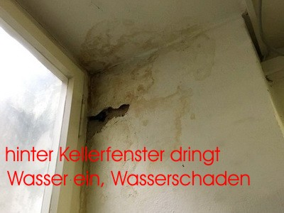 Wasser läuft über Loch in den Keller am Kellerfenster